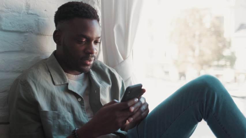 Handsome african american young man in the modern apartment sitting on windowsill looking through the window holding and checking a smartphone | Shutterstock HD Video #1047226843