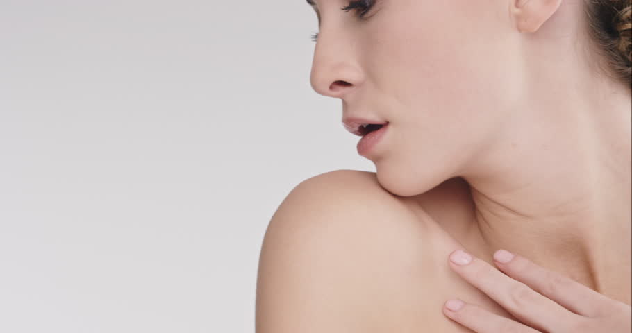 Close up beauty portrait of beautiful woman touching healthy skin and bare shoulders in slow motion skincare concept shot against grey background slow motion Red Epic Dragon
