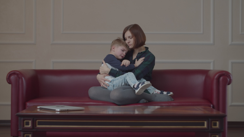 Young 30s mother consoling her little son at the time of disappointment. Kid crying on mom's knees. Woman hugging boy to comfort him.  Royalty-Free Stock Footage #1047235537