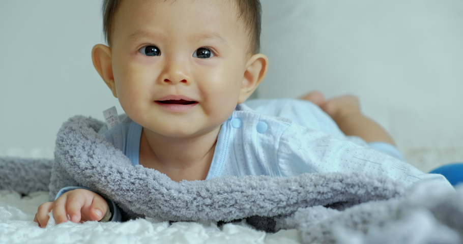 Close up of happy baby looking at camera and laying in bed with copy space. Asian baby boy. | Shutterstock HD Video #1047252448