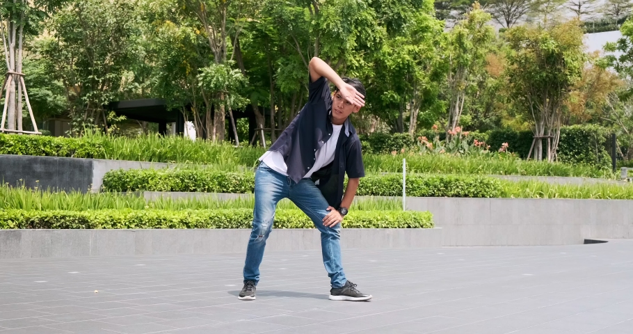 Young man doing street dancing with green trees and garden in background. Asian man.   Shutterstock HD Video #1047252571