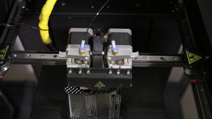 3D technology close up of the printer head printing a plastic part product