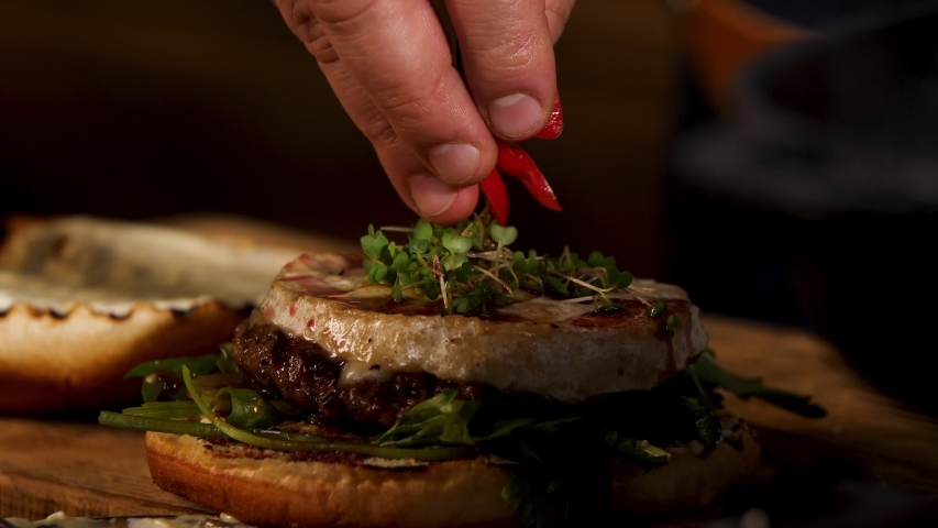 Delicious juicy red hot chili pepper burger with beef cutlet and camembert cheese, foodporn. Stock footage. Close up of male hand putting red circles of chili pepper in the burger. | Shutterstock HD Video #1047262543
