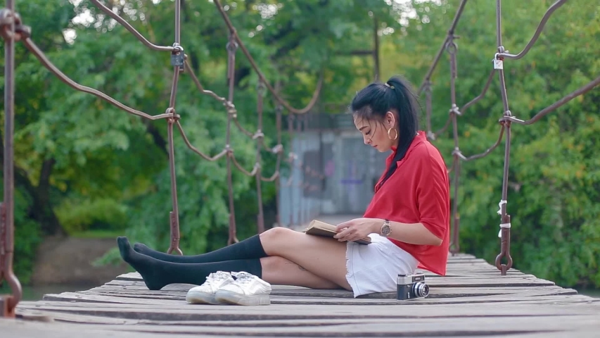 Krasnodar, Krasnodar/Russia - 09 05 2019: amazing charming cute brunette girl with beautiful black hair sits on suspension bridge over river and reads book against background of green trees