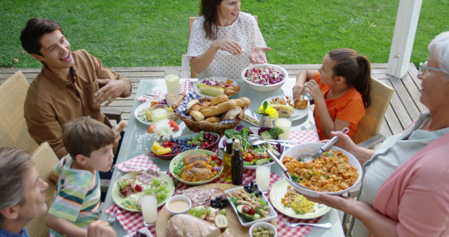 High angle view of a multi-generation Caucasian family outside at a dinner table set for a celebration meal, sitting, talking, standing and serving food, slow motion | Shutterstock HD Video #1047269671
