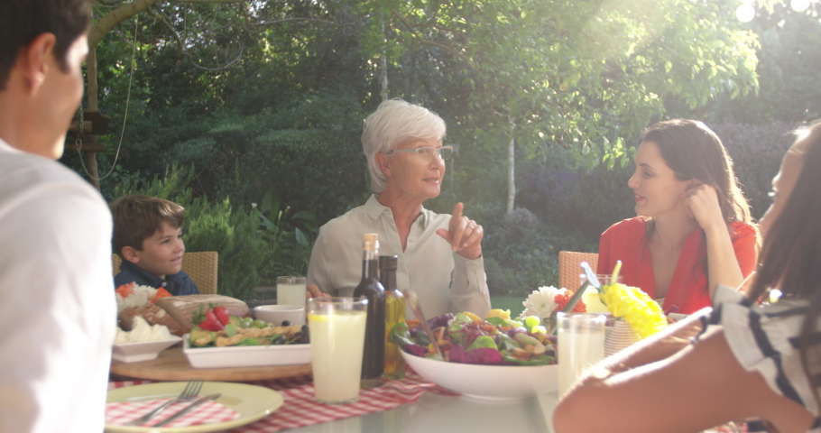 Front view of a senior Caucasian woman, her adult daughter and husband, grandson and granddaughter sitting outside at a dinner table set for a family meal, talking and smiling, backlit, slow motion #1047273469