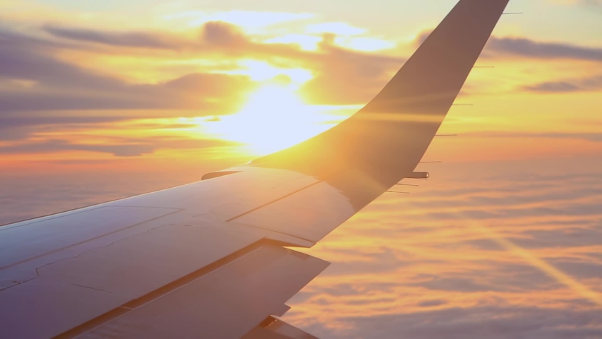 View of the wing of a passenger plane flying above dense clouds at sunset #1047293503