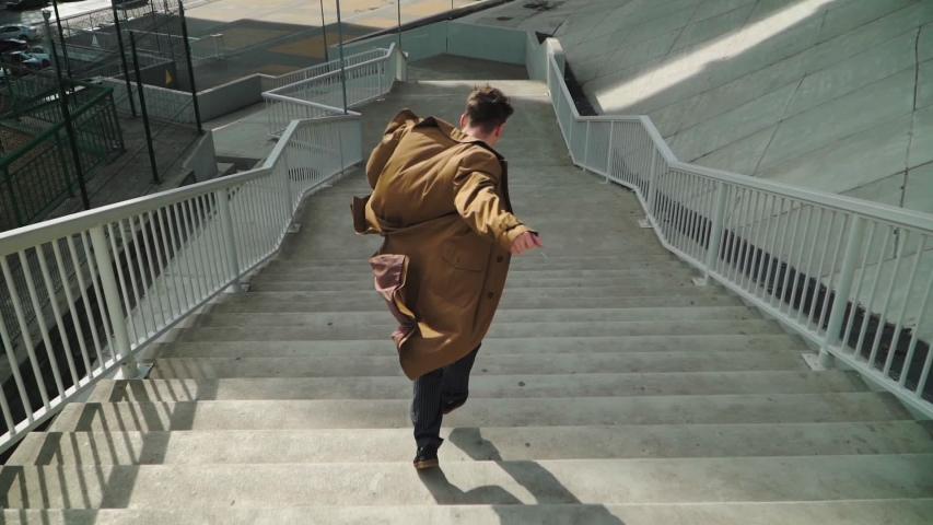 Happy Young Man Actively Dancing While Walking down the stairs. He's Wearing a brown long coat. Scene Shot in an Urban Park Next to Business Center. Slow motion. Shooting from the air. | Shutterstock HD Video #1047305755