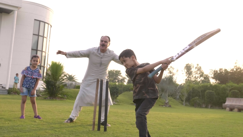 A young active boy batting hits the ball with the bat and celebrates outdoors. A male kid strikes the ball for four runs while playing cricket with his family members in the garden outside the house