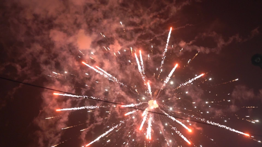 Amazing fireworks explosions at night sky salute party smoke closeup slow motion #1047326131