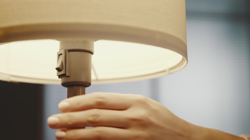 Woman turning on a table lamp at home, hand close up | Shutterstock HD Video #1047331333
