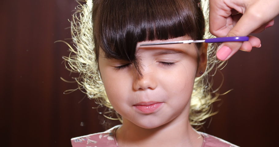 Mom or hairdresser cutting bangs to a little European girl of preschool age with brown hair and blue eyes in a pink dress on wooden background. Close up portrait slow motion 4k 50 fps | Shutterstock HD Video #1047342775