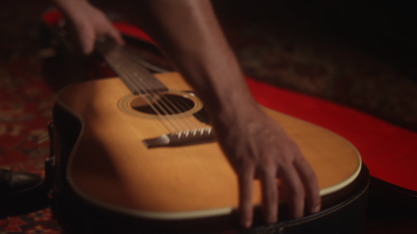 Close-up of a musician putting away his acoustic guitar into a guitar case after a performance and walks out of frame | Shutterstock HD Video #1047347536