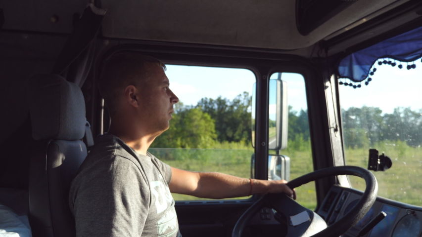 Man holds hand on the steering wheel and driving truck through countryside. Truck driver profile. Trucker sitting at the wheel of the car. Caucasian guy looks carefully at the road. Side view Close up Royalty-Free Stock Footage #1047359836
