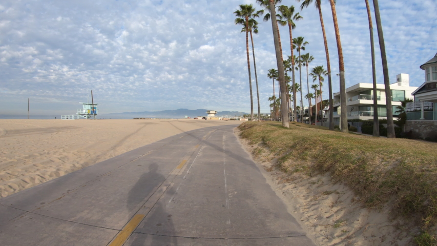 Early morning ride past homes and palm trees on the Venice beach bike path in Southern California. | Shutterstock HD Video #1047364000