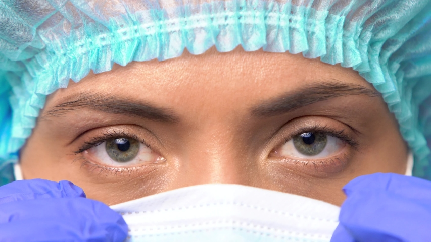 COVID-19. 2019 Novel Coronavirus (2019-nCoV) concept. close-up eyes of a young female doctor with a medical cap on her head puts on a medical face mask. on a blue background. Royalty-Free Stock Footage #1047364006