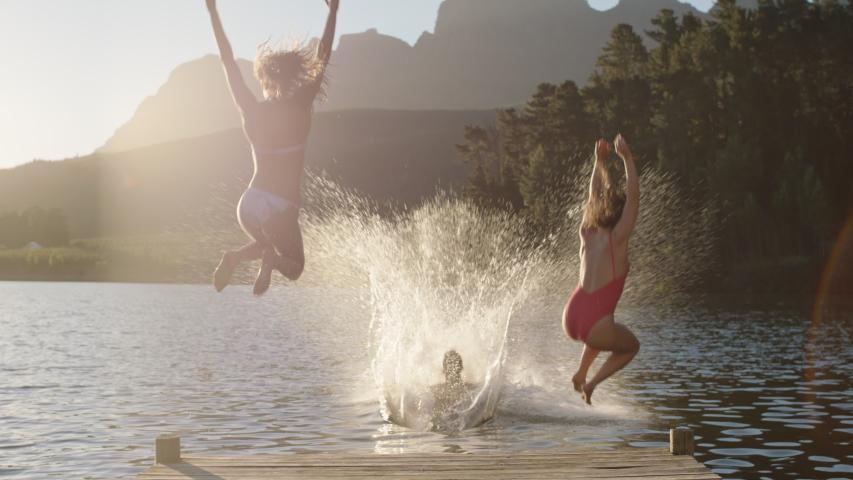 Happy friends running jumping off jetty in lake at sunset having fun splashing in water enjoying freedom sharing summertime adventure   Shutterstock HD Video #1047368257
