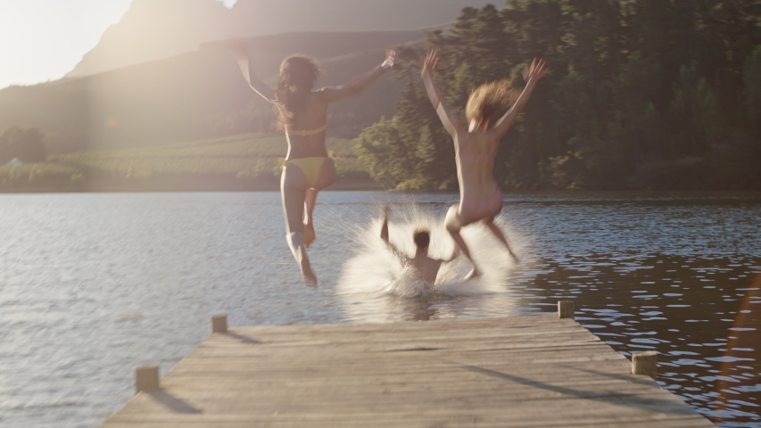 Happy friends running jumping off jetty in lake at sunset having fun splashing in water enjoying freedom sharing summertime adventure | Shutterstock HD Video #1047368401