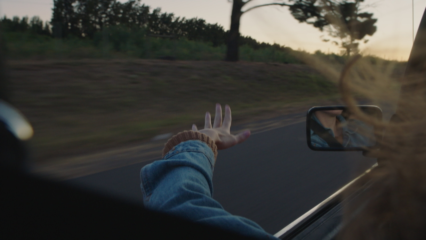 young woman in car holding hand out window feeling wind blowing through fingers driving in countryside on road trip travelling for summer vacation enjoying freedom on the road at sunset Royalty-Free Stock Footage #1047368974