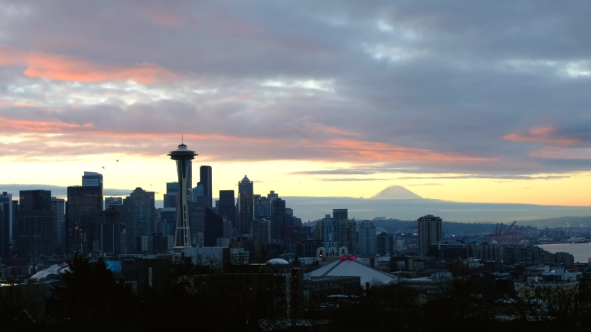 Seattle , Washington / United States - 02 09 2020: Sunrise, Space Needle, Seattle Skyline, and Birds Flying with Mt. Rainier in the Background
