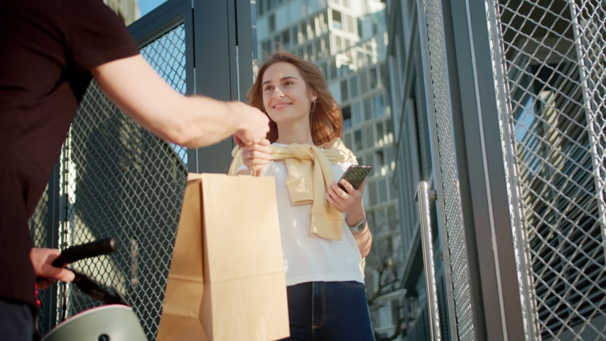 Beautiful Caucasian female accepting delivery service kraft bag from messenger outside, pleasant smiling young woman getting food from courier in black with bike opening entrance home door fence   Shutterstock HD Video #1047379930