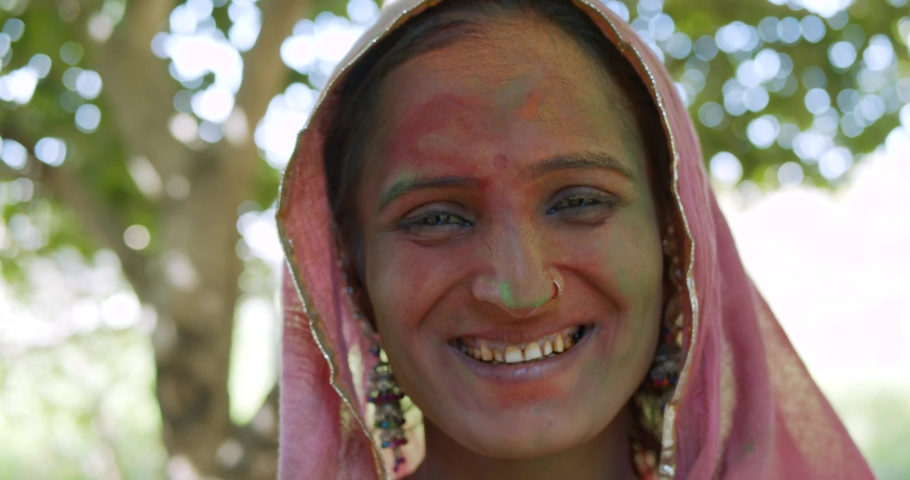 Close-up confident Holi color face of an Indian women wearing traditional costume sari dress and jewelry earrings as she smile in joy and happiness and looks at the camera for a photo video shoot pose | Shutterstock HD Video #1047382399