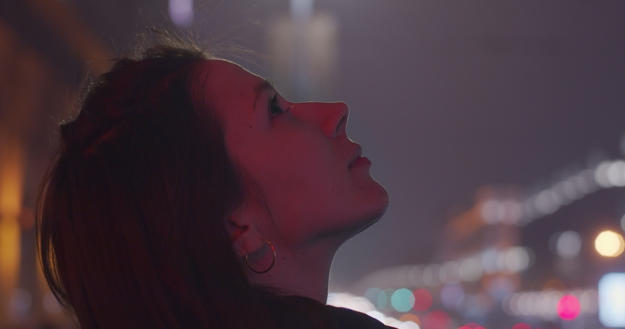 Profile portrait of Caucasian girl looking up outdoors shallow city traffic lights background copy space. Side view of young woman gazing to skies at night slow motion text. Freedom happiness dreams | Shutterstock HD Video #1047390931