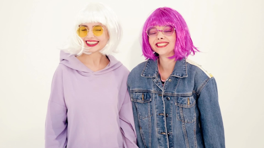 Two young beautiful smiling hipster girls in trendy summer clothes.Sexy carefree women posing in studio near white wall.Positive models dancing.They shaking their head in wigs.Female going crazy