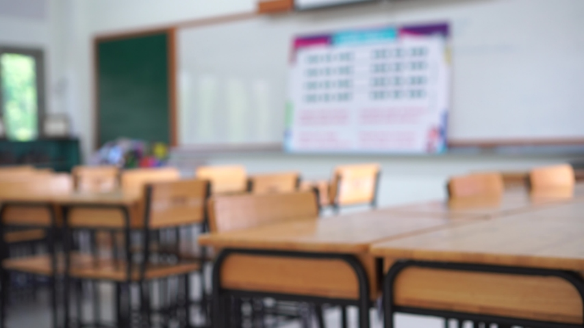 Blurred of Empty Classroom in lecture room or School with desks chair wood for studying lessons in high school Thailand, interior of secondary education, whiteboard and green board educational