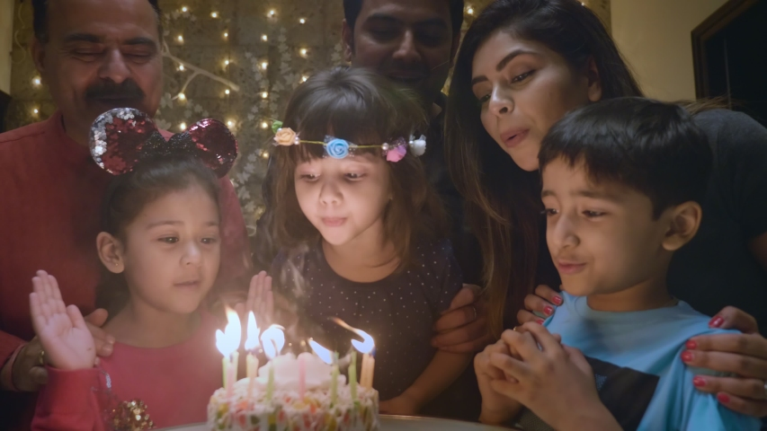 A wide shot of an adorable Indian girl child blowing candles on a cake and family and friends celebrating the occasion. A birthday celebration of a cute young girl surrounded by kids and dear ones.  Royalty-Free Stock Footage #1047397750