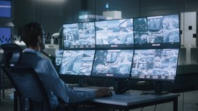 Industry 4.0 Modern Factory: Security Operator Controls Proper Functioning of Workshop Production Line, Uses Computer with Screens Showing Surveillance Camera Footage Feed. High-Tech Security