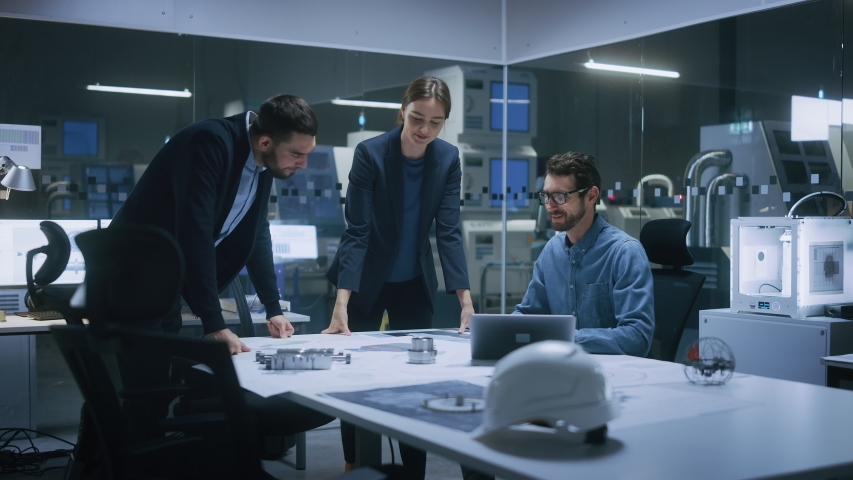 Modern Factory Office Meeting Room: Diverse Team of Engineers, Managers Talking at Conference Table, Look at Blueprints, Inspect Mechanism, Use Laptop. High-Tech Facility with CNC Machines Royalty-Free Stock Footage #1047399034