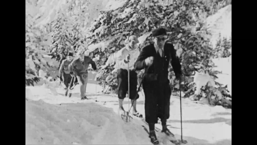 CIRCA 1936 - People go cross-country skiing and ride in horse-drawn sleighs through Garmisch-Partenkirchen in the Bavarian Alps.