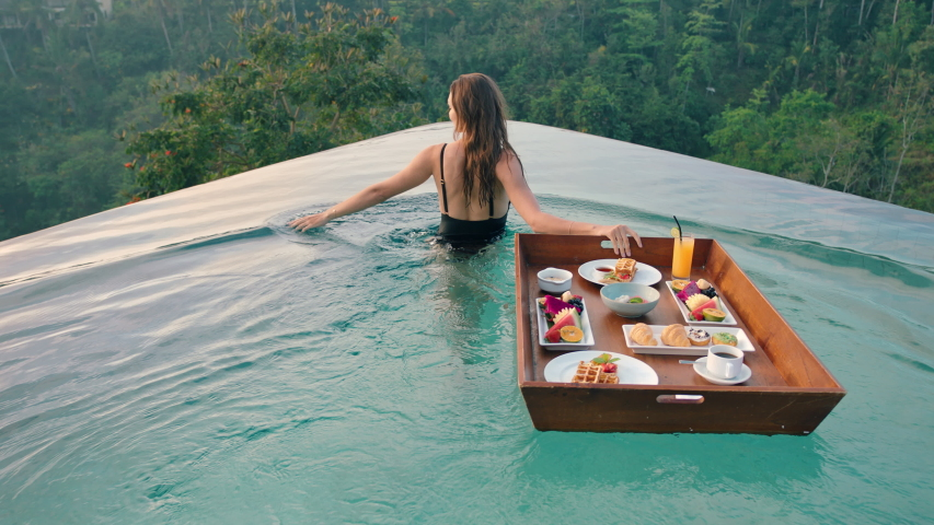 Travel woman having breakfast in swimming pool enjoying exotic food at luxury hotel spa with view of tropical jungle at sunrise
