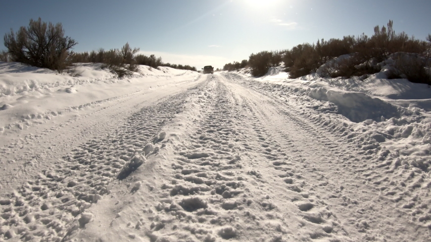 Driving on snow covered road winding through the desert following truck ahead as it makes way down the path.   Shutterstock HD Video #1047408490