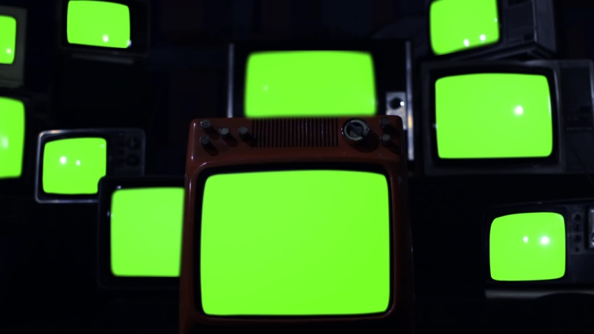 "Ten Old TVs turning on Green Screens. Dark Blue Tone. You can Replace Green Screen with the Footage or Picture you Want with ""Keying"" effect in After Effects (check out tutorials on YouTube).  