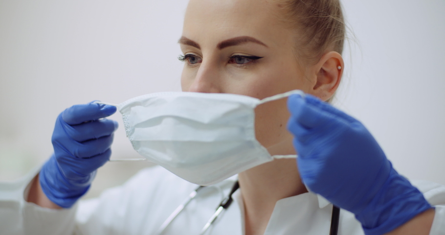 female doctor putting on protective mask at clinic Royalty-Free Stock Footage #1047412060