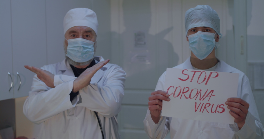 """Two doctors show stop-gesture and inscription """"Stop Corona-virus"""" in hospital cabinet. Slwoly in 4K 