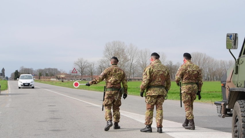 Castiglione d'Adda, Italy - 27 February 2020:Italian Military personnel wearing respiratory masks checks the border of the quarantine red zone as measures are taken to contain the Coronavirus outbreak
