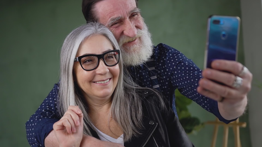 Close up of attractive loving senior couple where bearded man embracing his wife while she waving hand to their friend or relative on phone video chat
