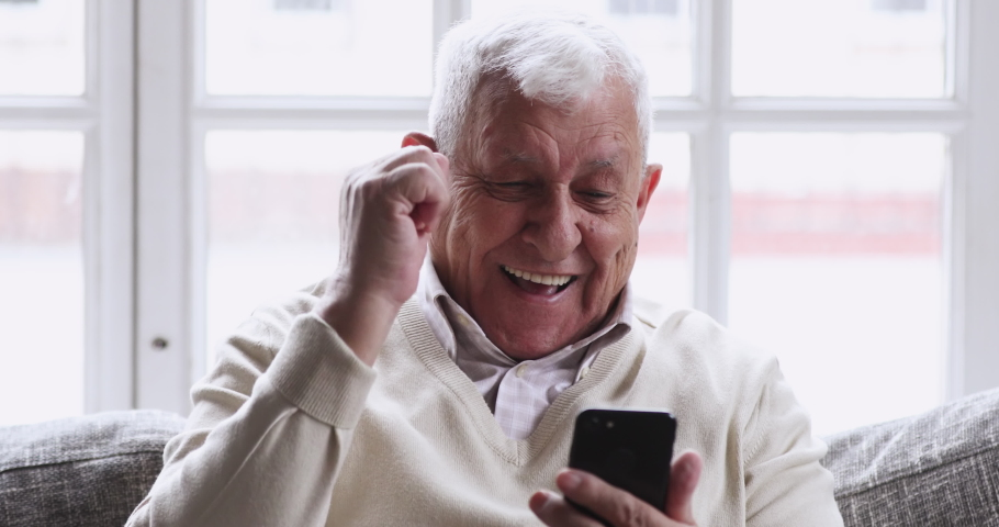 Overjoyed senior old 80s man hold phone look at screen excited about mobile app sport bet bid win concept. happy elder grandfather winner celebrate victory success read good news in cell text message.