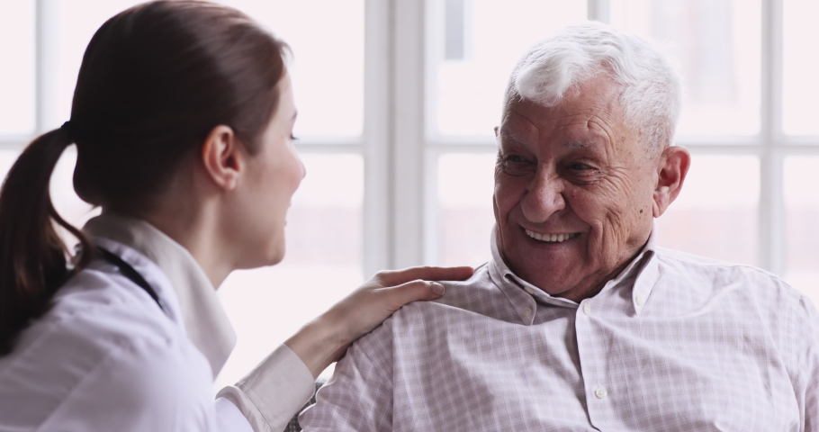 Smiling healthy senior elderly grandpa talk to caring young female doctor physician examining aged patient in hospital during medical checkup visit, eldercare treatment, old people healthcare concept.