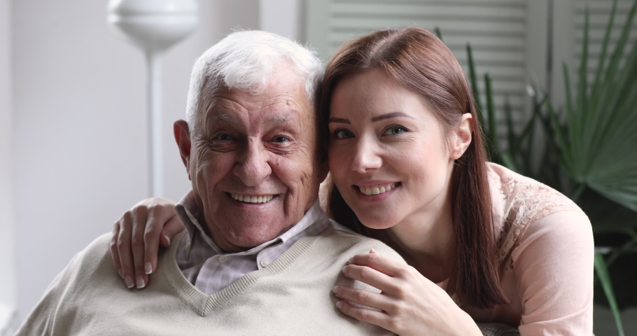 Loving smiling young adult granddaughter hug old elder grandfather at retirement home. happy grown grandchild cheerful face embrace senior grandpa bonding, close up 2 two age generation family #1047422599