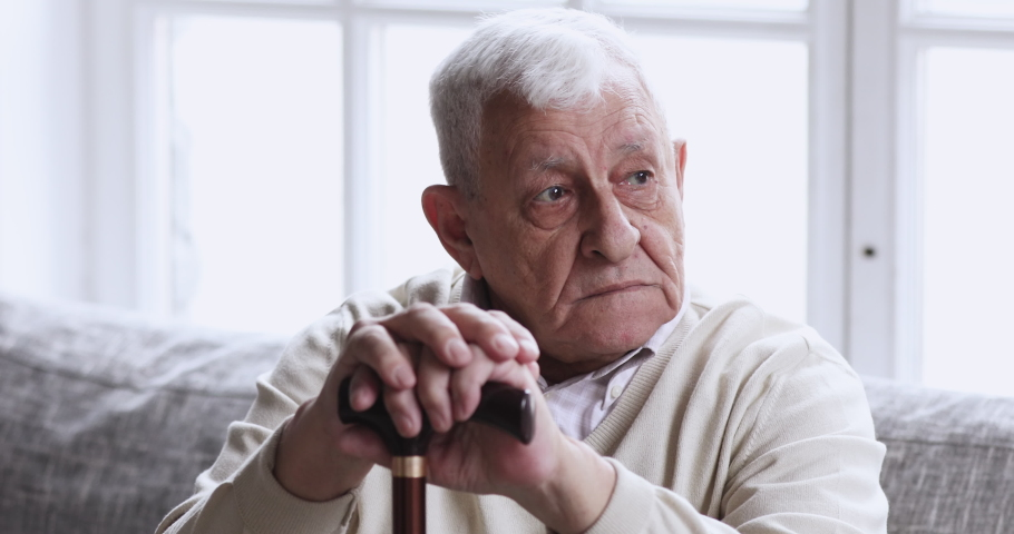 Sad lonely old elder grandfather hold cane stick sit alone on couch. Upset senior man having geriatric health problem walking difficulty concept think of solitude injury rehabilitation at nursing home