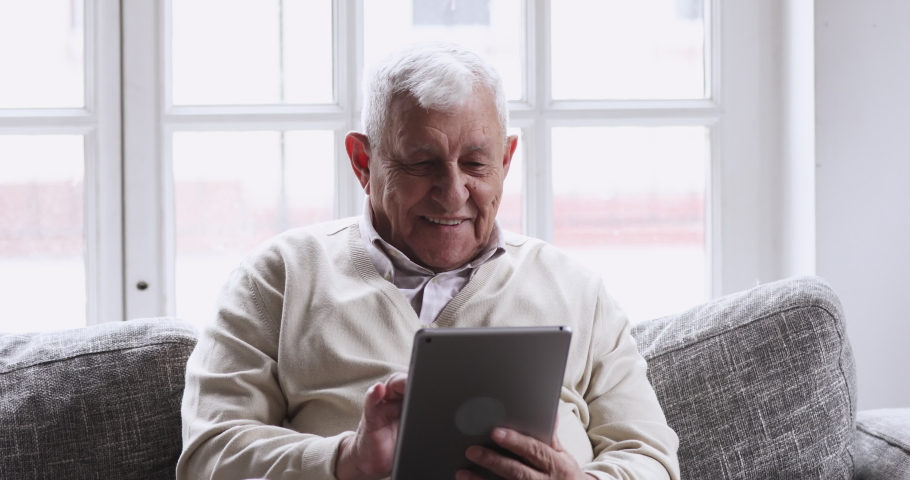 Smiling senior elder 80s man using digital tablet computer pad modern tech relax on sofa. Happy retired old grandfather browse internet read e book in app chatting online with distance doctor at home.
