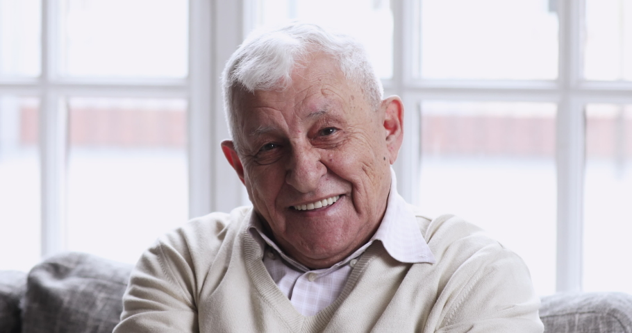 Happy elderly senior adult gray-haired 80s man smiling face white healthy teeth dental smile sit on sofa. relaxed old retired single grandfather posing alone at home look at camera, close up portrait. | Shutterstock HD Video #1047422632