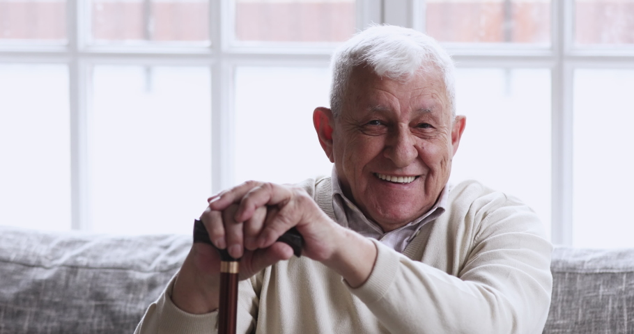Happy older senior adult man hold cane sit on sofa looking at camera. relaxed optimistic disabled retired elderly 80s grandfather dental smile posing with walking stick at nursing home, portrait