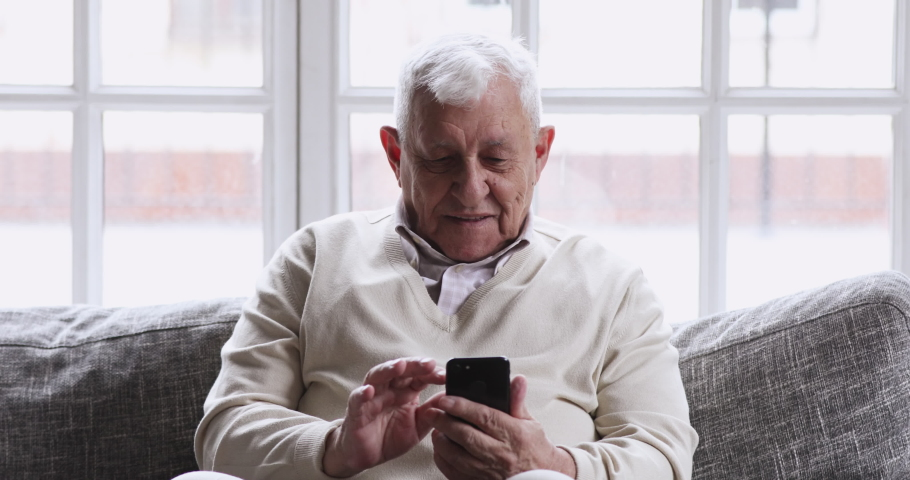 Smiling elder 80s adult grandfather learn mobile phone app sit on sofa, happy 70s senior man hold smartphone texting messages in social media reading news, old person using tech gadget concept at home Royalty-Free Stock Footage #1047425092
