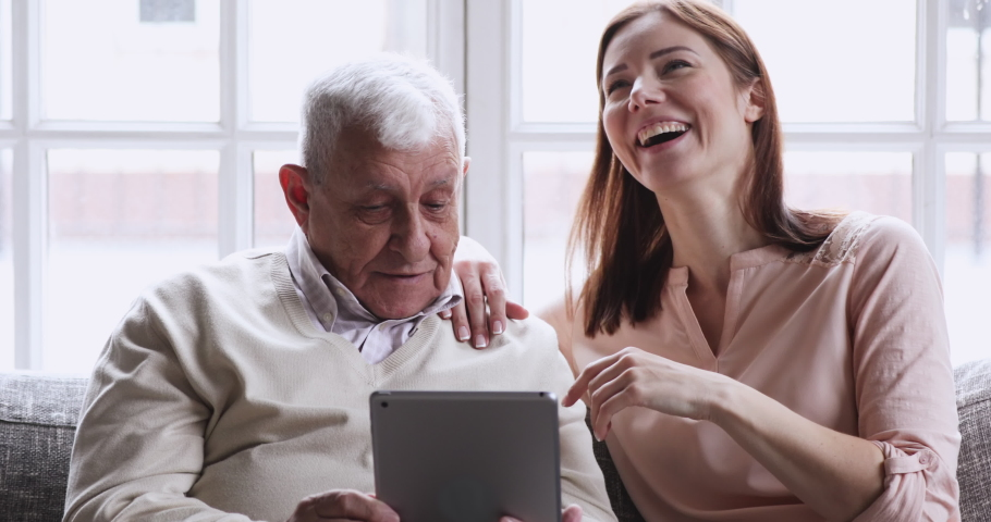 Grownup granddaughter teaching older grandpa using digital tablet. two age generations senior elder grandfather learning modern tech device concept with young adult daughter sit on couch at home