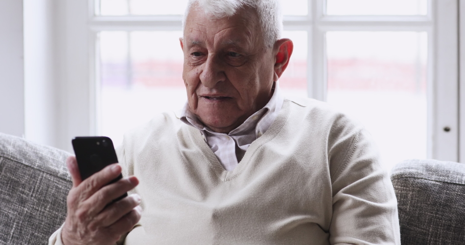 Happy senior elderly 70s man user holding smart phone watching mobile video calling online looking at screen relaxing on couch at home, older grandparent learn using modern technology gadget concept.
